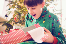 Surprised Boy Looking At Gift Box During Christmas