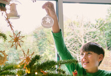 Cute Boy Decorating Christmas Tree By Window At Home