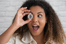 Excited Woman With Mouth Open Covering Eye With Bitcoin In Front Of Wall