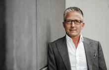Businessman Wearing Eyeglasses Leaning On Gray Wall
