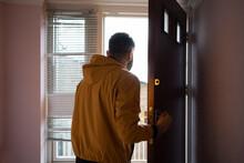 Man In Yellow Jacket Opening Door