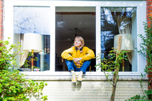 Mature Woman Looking Up While Sitting On Window Sill At Home