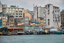 Istanbul Turkey. Karakoy Shore Of Istanbul And Many Pedestrian Ferry Anchored In Golden Horn With Small Fishing Boat During Overcast And Rainy Day In Istanbul.
