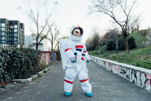 Female Astronaut With Alien Mask Standing On Footpath