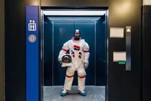 Male Astronaut With Space Helmet Standing In Elevator