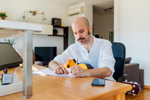 Male Music Composer With Guitar Writing Musical Notes At Table In Living Room