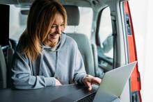 Smiling Businesswoman Working On Laptop In Van