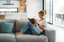 Female Freelancer Sitting On Sofa While Reading Book At Home