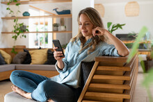 Blond Hair Woman Text Messaging Through Smart Phone While Sitting In Living Room