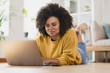Smiling Woman Using Laptop While Lying Down At Home
