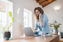 Smiling Female Professional Talking On Smart Phone While Working On Laptop At Desk