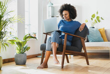 Smiling Woman Using Laptop While Sitting On Armchair At Home