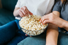 Female Friends Sharing Popcorn At Home