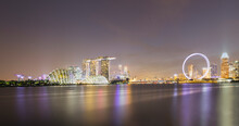 Singapore, Long Exposure Of Marina Bay At Night With Marina Bay Sands Hotel And Singapore Flyer In Background