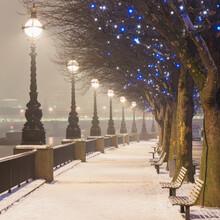 UK, England, London, Row Of Street Lights Illuminating Empty Snow-covered Promenade