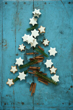 Christmas Cinnamon Star Shaped Cookies Together With Cinnamon And Needle Branches Arranged In Christmas Tree On Blue Rustic Wooden Background