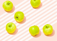 Studio Shot Of Six Green Apples Lying Against Pink Striped Background