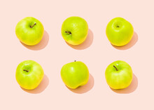 Studio Shot Of Six Green Apples Lying Against Light Pink Background