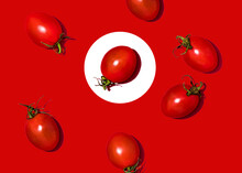 Studio Shot Of Cherry Tomatoes Lying Against Red Background