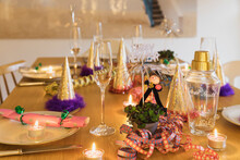 Festive Laid New Years Eve Table With Plates, Candles, Party Hats, Champagne Flutes And Chimney Sweep Figurines