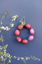 Blossoming Twigs And DIY Wreath Made Of Red Spotted Easter Eggs