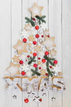 Arrangement Of Homemade Cookies And Various Christmas Decorations Hanging On Wooden Wall