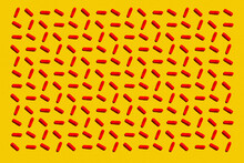 Pattern Of Rows Of Red Medicine Capsules Laid Against Yellow Background