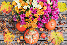 Autumn Harvest Including Bouquet Of Blooming Chrysanthemums, Various Nuts, Apples, Pumpkin, Squashes And Grape Leaves
