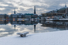Germany, Hamburg, City Architecture Reflecting In Binnenalster Lake At Sunset In Winter