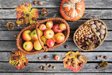 Autumn Harvest On Garden Table: Apples, Nuts And Chestnuts In Baskets And Edible Pumpkin