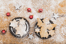 Christmas Ornaments And Fresh Homemade Cookies Lying On Wooden Surface