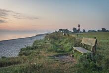Germany, Schleswig-Holstein, Pommerby, Empty Beachside Bench At Dusk With Falshoft Lighthouse In Background