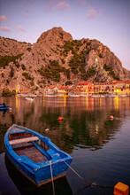 Croatia,Split-DalmatiaCounty, Omis, Rowboat Moored In Front Of Coastal Townat Dusk
