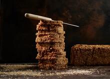 Studio Shot Of Kitchen Knife Lying On Top Of Stack Of Fresh Wholegrain Bread Slices