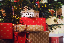 Stack Of Gifts In Front Of Christmas Tree At Home