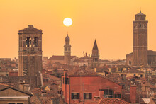 Italy, Veneto, Venice, Church Bell Towers Rising Over Surrounding Houses At Moody Sunset