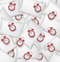 Tiny Alarm Clocks On White Pillows