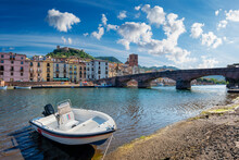 Riverside View Of Bosa Town With A Beautiful Blue And Cloudy Sky, The Old Bridge And The Colorful Houses In Background And A Little Boat In Foreground.