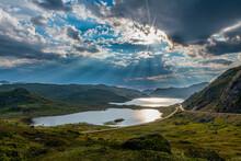 Norway, Setesdalen, Sun Breaking Through Clouds Over Lake