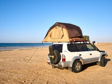 Tent Pitched On Top Of Roof Of Off-road Vehicle Parked On Sandy Coastal Beach