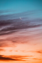 Crescent Moon Glowing Against Red And Blue Sky At Dusk