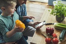 Boy Sitting With Father Holding Bell Pepper While Pointing At Smart Phone