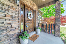 Rustic Style Decoration Of Veranda With A Stone Masonry Wall, Flower Door Wreath, And Flower Vases