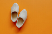 Typical One Single Pair Of Handmade Wooden Shoes On Orange Background With Free Copy Space, Orange Fever Is A Phenomenon In The Netherlands That Occurs During Major Events In Dutch Culture.