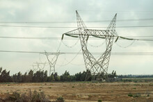 Power Lines In Desert Against A Cloudy Sky