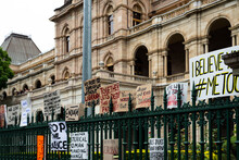 Protest Signs On A Green Wrought Iron Fence With A Grand Old Sandstone Building Behind.