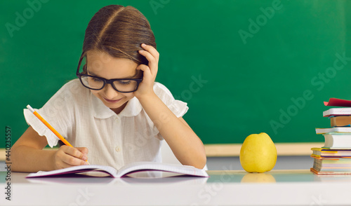 Fotografiet Concentrated schoolgirl child writing in copy-book while sitting at desk with apple and stationary study supplies against green chalkboard