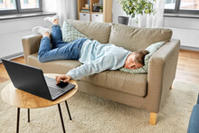 People, Boredom And Depression Concept - Bored Or Lazy Young Man With Laptop Computer Lying On Sofa At Home