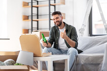 Moving, People And Real Estate Concept - Happy Smiling Man With Box Of Pizza And Beer Bottle At New Home Showing Thumbs Up