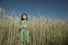 Asian Girl In Green Dress Standing In The Middel Of A Wheat Grain Field Under Blue Sky In Summer